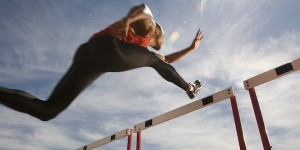 Athlete jumping over hurdle on track