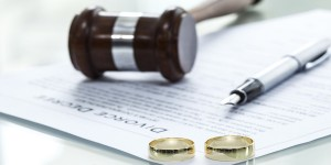 Divorce decree and wedding rings with pen and gavel