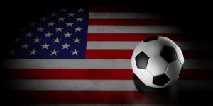 Football on American flag under spotlight