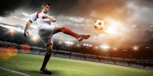 Football player on field kicking ball