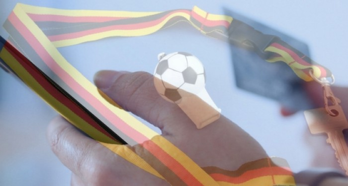 Hand holding phone with german football and whistle in background
