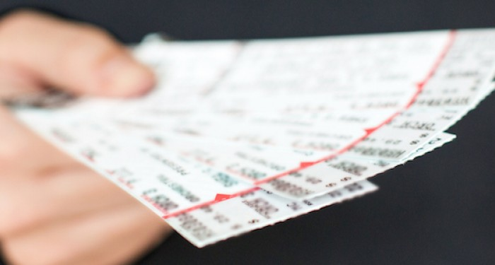 A person holding sports tickets in their hand