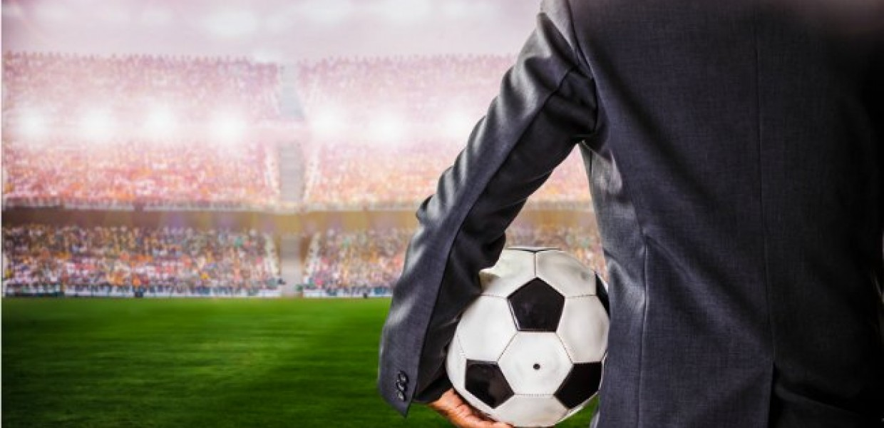 Suited man holding football