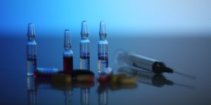 Syringe and capules on blue background