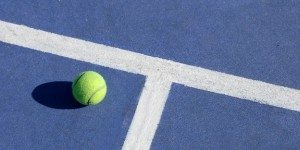 Tennis ball on blue court