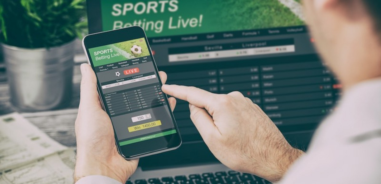 Man betting on sport on a phone with laptop open